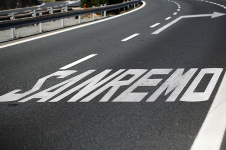 road surface: Photo closeup of asphalt road surface marker Sanremo on paved roadway for guidance and information to drivers direction sign on grey background, horizontal picture Stock Photo