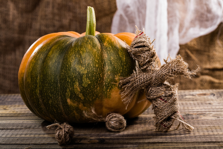 damnation: Halloween concept of spooky rag doll with two clews of twine near big round pumpkin with green spot on wooden table on white and brown cloth background, horizontal photo