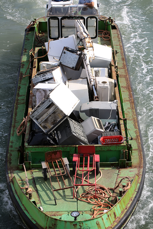 domestic appliances: Photo seen from above of sea open hopper barge full of used domestic appliances recycling material garbage riding on blue waves water splashes on seascape background, vertical picture