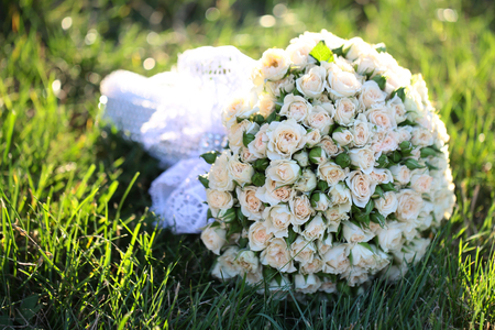 nuptials: Beautiful bridal fresh floral decoration bouquet of champagne splendid tender roses buds flowers for nuptials marriage day on green grass background outdoor closeup, horizontal picture Stock Photo