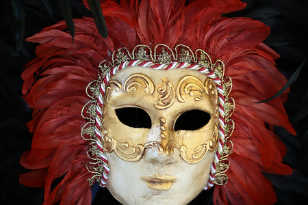 distinctive: Photo closeup of one distinctive Venetian carnival mask with beautiful decoration of natural red feathers classic accessory for sale outdoor on wall on black plume background, horizontal picture