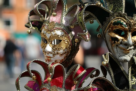 and distinctive: Photo closeup of distinctive Venetian carnival masks with beautiful decoration hand painting ornate classic accessory on display for sale outdoor on blurred background, horizontal picture