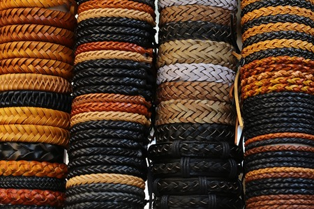 waistband: Photo closeup of many different male and female braided leather belts different colors fashion accessory stacked on display for sale outdoor on white background, horizontal picture