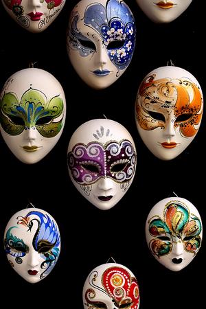mascaras de carnaval: Foto del primer de muchas máscaras venecianas de carnaval distintivos de varios colores de pintura a mano hermosa decoración clásica entre los accesorios para la venta al aire libre en la pared sobre fondo negro, imagen vertical