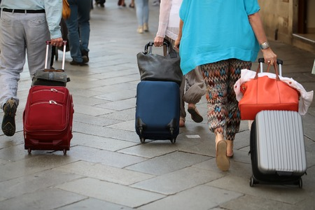 flagstone: Photo back view of people men women walking and rolling suitcases wheeled travel bags trolley cases along flag-stone pavement on streetscape background, horizontal picture Stock Photo