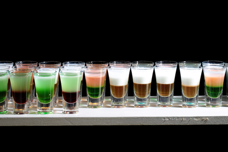 shooters: Line of many drinking small glasses with tasty alcoholic shooters shots cocktail drinks green red white and orange colored beverage standing on bar happy night party on black background, horizontal Stock Photo
