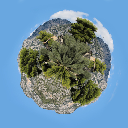 hemisphere: Photo seen from above ultra wide strong hemisphere image of visual distortion fisheye effect of stony cottage among green trees on tops of mountains white clouds on blue sky background, square picture Stock Photo