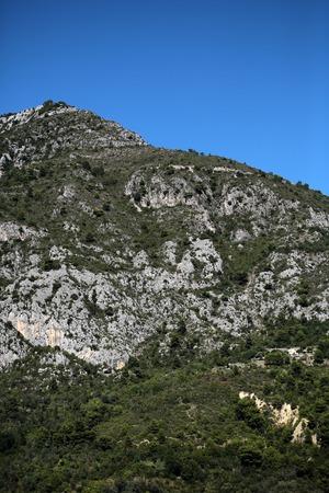 plan éloigné: Photo long shot de belles têtes sommets de montagnes avec des falaises et des arbres à feuillage vert élévation naturelle de la surface de la terre sur le ciel bleu vif sur fond de paysage, image verticale Banque d'images