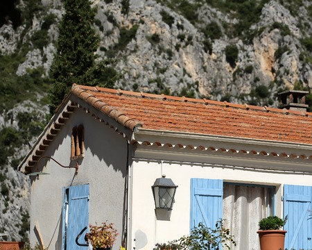 mountain scene: Photo closeup of white plastered facade of lovely small cottage farmhouse with open blue shutters and brown tiled roof on mountain scene background, horizontal picture Editorial