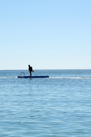 self contained: Photo long shot of one skin-diver in diving suit standing on float board offshore in calm blue sea silhouetted against clear sky day time summer on beautiful seascape background, vertical picture Stock Photo