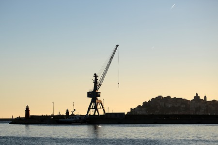 plan éloigné: Photo long shot of sea port terminal modern yacht crane pierhead light outlines of city against calm evening marine and dim dusk blue sky on seascape background, horizontal picture Banque d'images