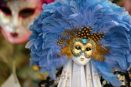 and distinctive: Photo closeup of one distinctive golden Venetian carnival mask with beautiful decoration of natural blue feathers classic accessory for sale outdoor on wall on blurred background, horizontal picture