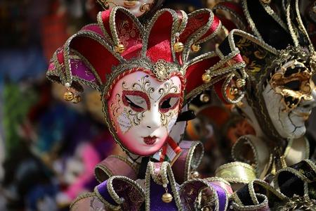 Foto primo piano di distintivi maschere di carnevale veneziano con bella decorazione mano pittura accessorio per eccellenza ornato in esposizione per la vendita all'aperto su sfondo sfocato, immagine orizzontale