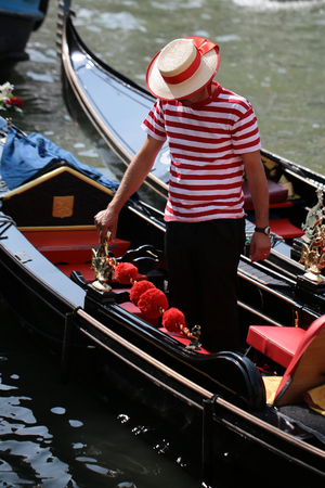 waterscape: Photo closeup of one male gondolier dressed in straw boater and stripy vest standing in traditional black flat-bottomed Venetian rowing boat gondola on waterscape background, vertical picture