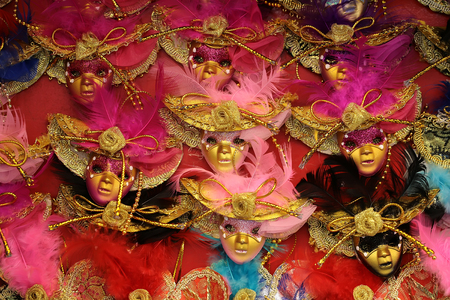 distinctive: Photo closeup of many distinctive Venetian carnival masks of various colors with natural feathers beautiful decoration classic accessory for sale outdoor on wall on red background, horizontal picture Stock Photo