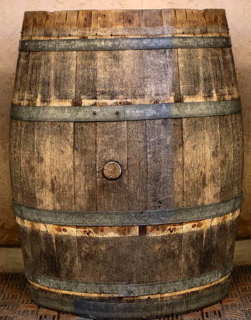 hogshead: Photo closeup of traditional wine oak wood barrel cask tierce hogshead coopered wooden container closed with cork on wall background, vertical picture