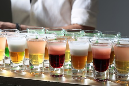 shooters: Many cold multicolored red yellow orange white alcoholic tasty shooters cocktail drinks in small transparent glasses standing in line on bar in background of man closeup indoor, horizontal pciture