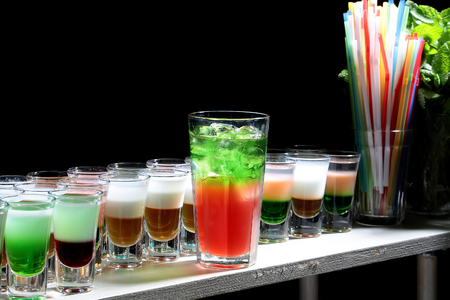 shooters: Glass of beautiful tasty sweet bright red green cocktail beverage with cold ice standing on bar near row of multicolored shots drinks and sipping straws closeup studio on black background, horizontal