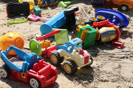 fun activity: Variety of childish colorful cars lorry plastic small toys laying on sand background summertime fun activity artificial construction closeup outdoor, horizontal picture