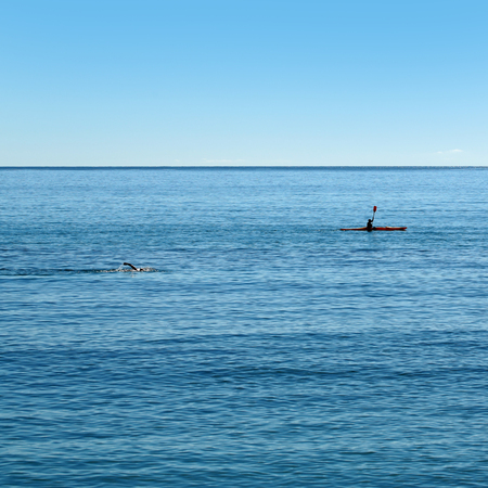 plan éloigné: Photo long shot of people swimming and rowing canoe paddling in calm blue sea silhouetted against clear sky day time on seascape background, square picture