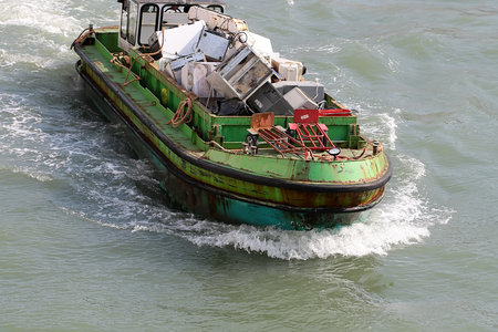 domestic appliances: Photo closeup of sea open hopper barge full of used domestic appliances recycling material garbage riding on blue waves water splashes on seascape background, horizontal picture