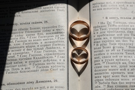 nuptial: Pair of male and female wedding golden beautiful fashion graceful rings having shadow of heart shape laying on white holy bible happy nuptial ceremony day closeup, horizontal picture Stock Photo
