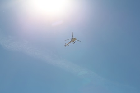 long shot: Photo long shot from below of one helicopter hovering in clear blue sky sunny day on celestial background, horizontal picture