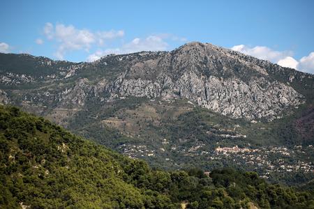 plan éloigné: Photo long shot de grands arbres à feuilles persistantes sur de belles têtes sommets des montagnes avec des falaises élévation naturelle de la surface de la terre des nuages ??blancs sur ciel bleu sur fond de paysage, image verticale