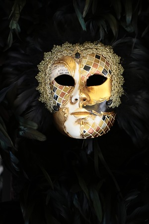 distinctive: Photo closeup of one distinctive golden Venetian carnival mask with beautiful decoration of natural black feathers classic accessory for sale outdoor on wall on plume background, vertical picture Stock Photo