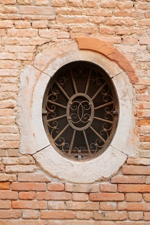 clay brick: Photo closeup of decorated old dirty dusty oval window with guard with ornamental aged rusty metal burglar bars on terracotta clay brick wall on mural background, vertical picture