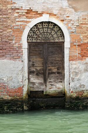 stucco facade: Photo closeup of one aged wet venetian street front entrance unpainted wooden door terracotta clay brick and rough stucco facade wall exterior building canal on cityscape background, vertical picture