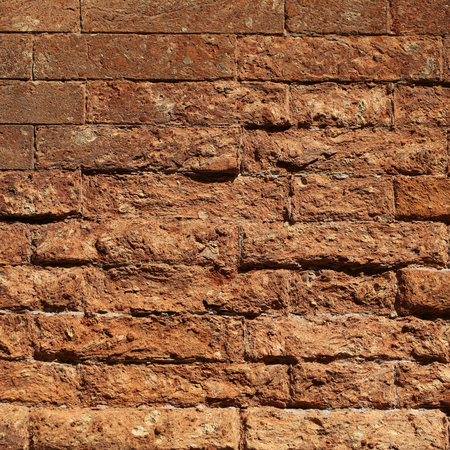 building materials: Photo closeup outdoor aged terracotta rough textured clay brick stone facade wall exterior building materials for masonry construction on mural background, square picture