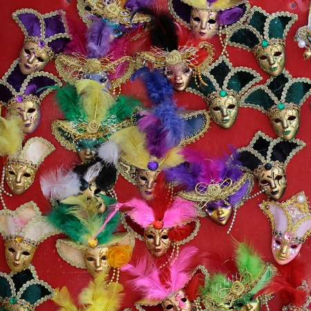 distinctive: Photo of many distinctive Venetian carnival masks of various colors with beautiful decoration natural feather classic accessory on display for sale outdoor on wall on red background, square picture
