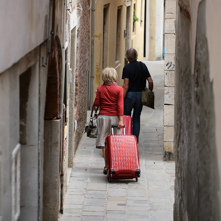 Photo back view of silver-haired senior couple aged man and woman walking and rolling suitcases wheeled travel bags trolley cases along narrow street on cityscape background, square picture