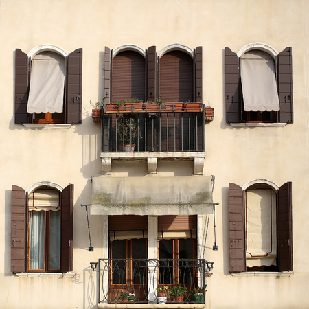 louver boards: Photo closeup of beige plastered facade of town house windows shut with sun-blinds louver-boards roller blinds and open brown shutters two balconies flower pots on cityscape background, square picture