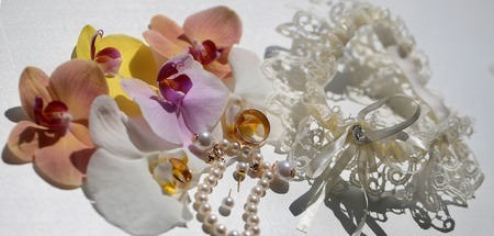 wedding accessories: Beautiful adorable bridal wedding accessories pearl bracelet earrings golden rings lacy retro garter decorated with petals of yellow pink orchids on white background closeup panorama image, horizontal Stock Photo
