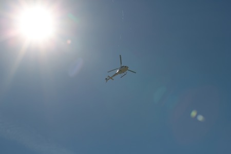 plan éloigné: Photo long shot from below of one helicopter hovering in clear blue sky sunny day sun spot on celestial background, horizontal picture Banque d'images