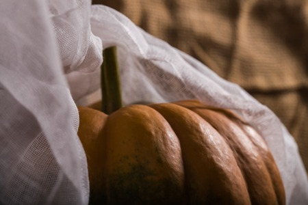 Top part of orange squash with stem smooth segmented surface covered with white cheesecloth on burlap background, horizontal photo
