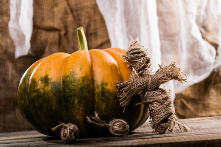 damnation: Halloween concept of magical burlap doll with two balls of twine near big round cucurbita with green blotch on wooden table on white and brown fabric background, horizontal photo