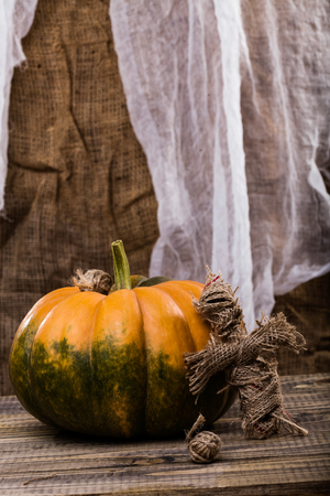 cross linked: Handmade cross shaped Halloween sackcloth puppet with two tangles of twine with round orange squash with green blotch on wooden table on white and brown cloth background, vertical photo