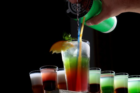 shooters: Beautiful delicious sweet bright red and green alcohol cocktail in transparent drinking glass with sipping straws pouring from shaker near many colorful shots on black background closeup, horizontal