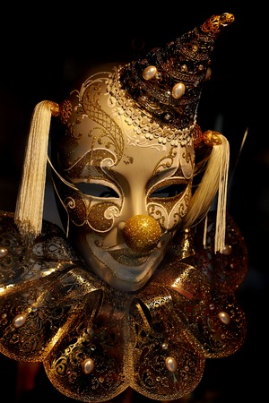 distinctive: Photo closeup of one beautiful traditional ornate hand painted distinctive golden mask of fool clown in cap with tassels collar decorated classic accessory on black background, vertical picture