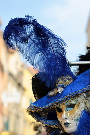 distinctive: Photo closeup of one distinctive golden Venetian carnival mask with beautiful decoration in blue hat with natural feather classic accessory for sale outdoor on streetscape background, vertical picture