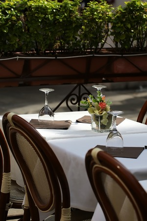 Tissues: Photo closeup of restaurant table set with upside down tall wine glasses brown paper tissues white tablecloth classic chairs flowers in pots on outdoor background, vertical picture