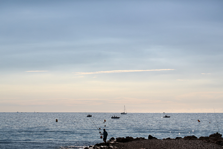 plan éloigné: Photo long shot of beautiful evening marine fisherman and vessels offshore in calm blue sea silhouetted against milky cloudy sky on seascape background, horizontal picture