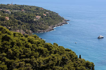 plan �loign�: Photo long shot of picturesque resort town hideaway among evergreen trees on mountain slope against blue sea on beautiful seascape background, horizontal picture