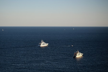 blue vessels: Photo of modern white ships yachts boats speed vessels offshore in calm blue sea silhouetted against clear sky day time on seascape background, horizontal picture