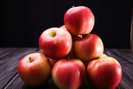 pyramid shape: Bunch of big beautiful tasty ripe red yellow apples in pyramid shape on wooden table on black background, horizontal photo