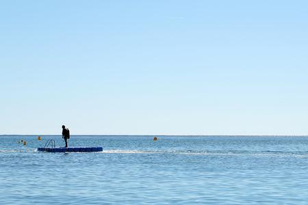 plan éloigné: Photo long shot d'une peau plongeur en scaphandre debout à bord flottant en mer dans la mer bleu calme silhouette contre un ciel clair d'été de jour sur le magnifique paysage de fond, l'image horizontale