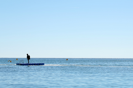 skindiver: Photo long shot of one skin-diver in diving suit standing on float board offshore in calm blue sea silhouetted against clear sky day time summer on beautiful seascape background, horizontal picture